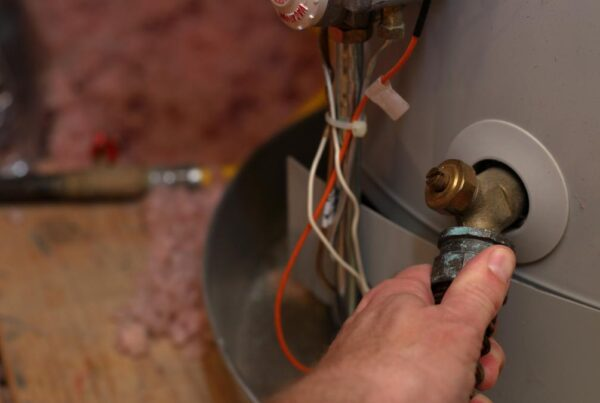 Close up of a hand attaching a hose to a hot water tank.