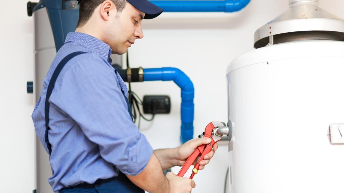 Technician repairing a hot water tank.