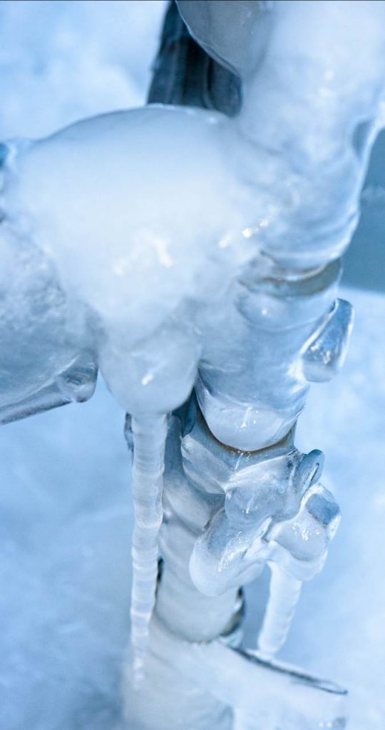 An outdoor pipe covered with ice.