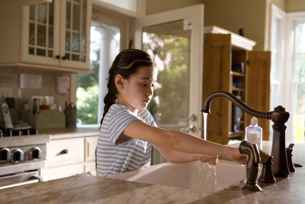 Young girl washing her hands in a kitchen sink.