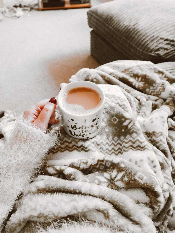 Woman's hand with red nail polish holding a cup of coffee above a blanket covering her lap.