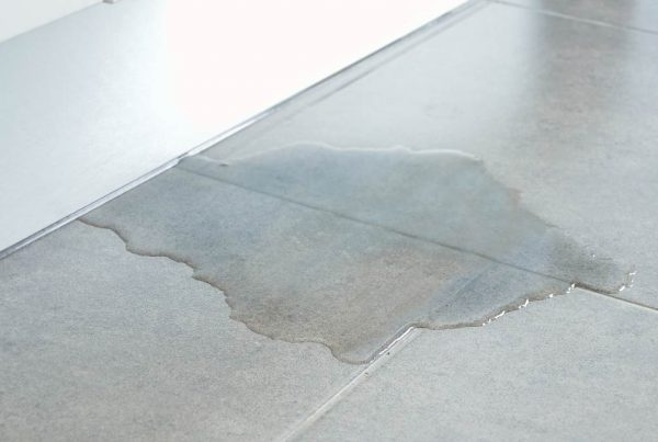 Water pooling underneath a door onto a grey tile floor.