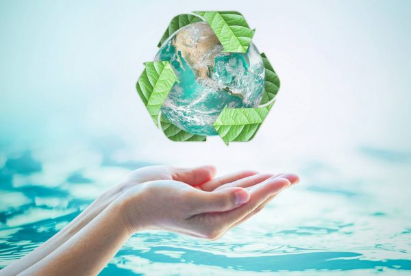 Hands reaching out below a graphic of the earth with green recycling symbol around it, against a blue water background.
