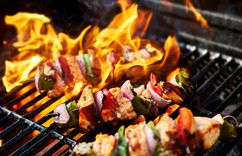 Chicken kebabs cooking on a flaming grill.