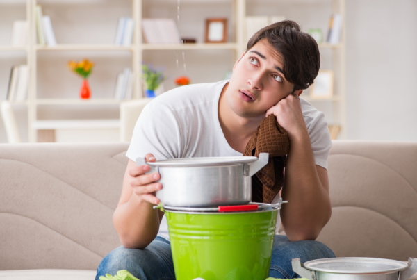 Man sitting on a couch holding a bucket under a leak.