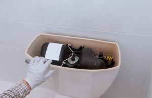 Gloved hand reaching into an open toilet tank.