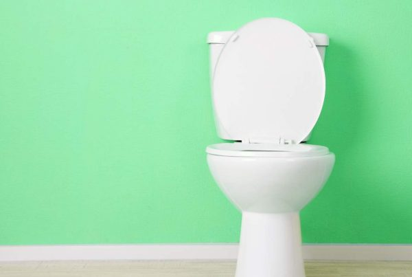White toilet against a green wall.