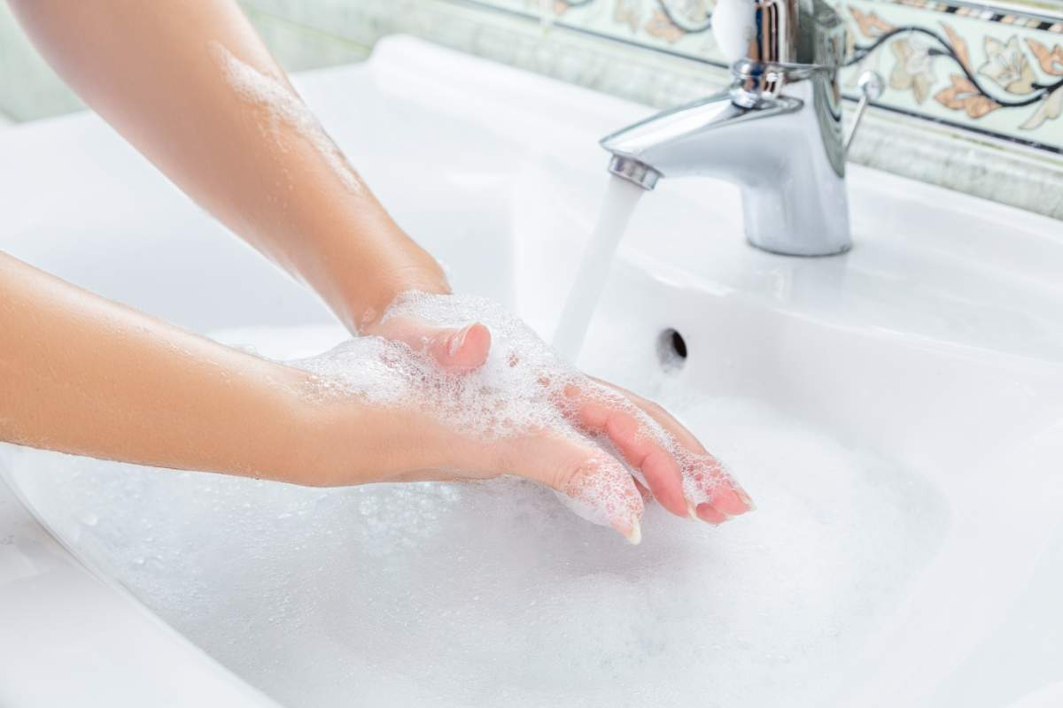 Closeup of a sudsy pair of hands under a running faucet.