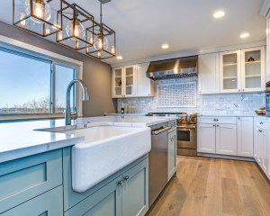 kitchen with pale blue cabinetry and deep white sink