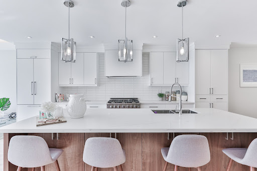 White kitchen with an island and barstools.