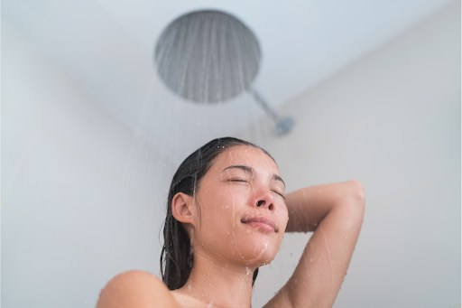 Woman taking a shower under a large round showerhead.