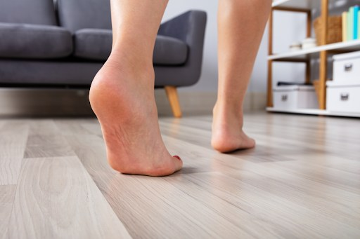 A pair of bare feet walking on a wood floor.