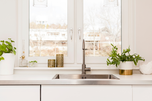 A kitchen with a chrome sink and white countertops.
